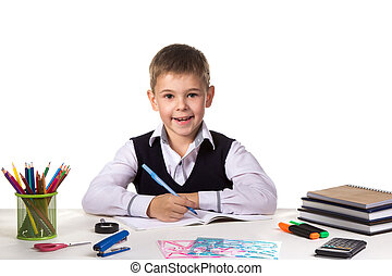 Cute cheerful pupil sitting still at the desk, surrounded with stationery