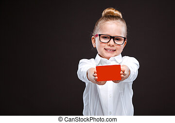 Cute cheerful young girl in white shirt and black trousers hold red card