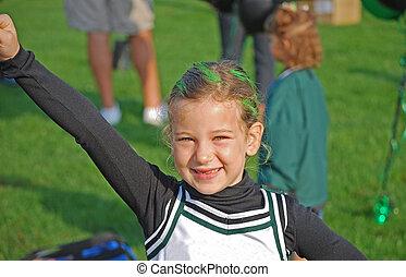 cute cheerleader - a happy cheerleader practices her routine