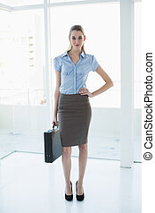 Cute chic businesswoman posing with hand on hip holding a briefcase looking at camera