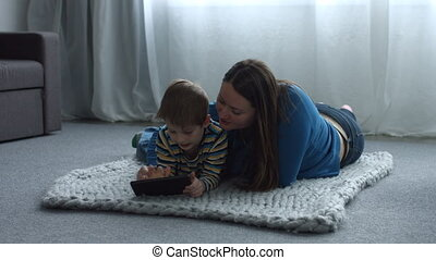 Cute child and mom with tablet pc relaxing at home