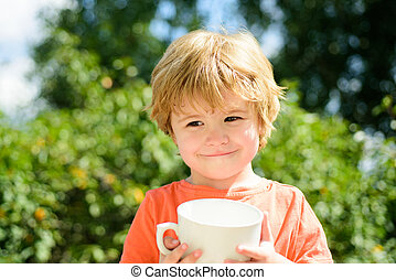 Cute child and tea or milk. The kid drinks fresh juice in nature. Boy holding a white cup. Handsome boy with a smile. Shy kid