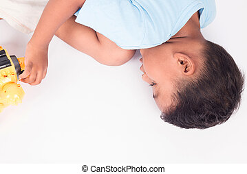 Cute child asian little boy lying on the floor and playing toy