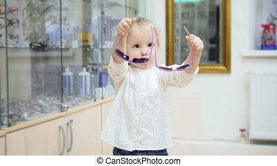 Cute child - blonde Girl dancing and asks mommy to buy colorful glasses in medical store - shopping in clinic