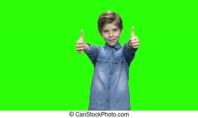 Cute child boy in denim jacket showing two thumbs up. Green...