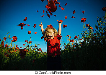 Cute child boy in poppy field. Very happy kid in poppy field. Happy little boy with a petals of poppies. Happiness in nature. Big smile from kid.