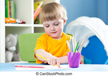 Cute child boy is drawing with color pencils in nursery