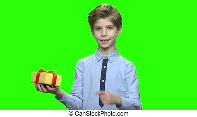 Cute child boy pointing at gift box.