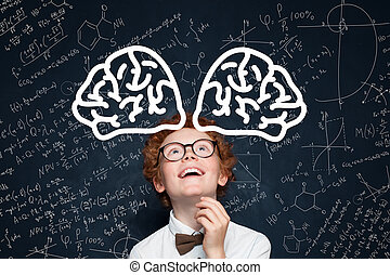 Cute child boy student in glasses having fun against blackboard background with science formulas