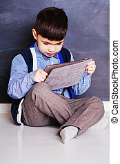 Cute child boy with pc tablet