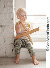Cute Child Boy with Wooden Plane Toy at Home