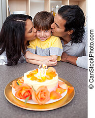 Cute child celebrating his birthday with his parents