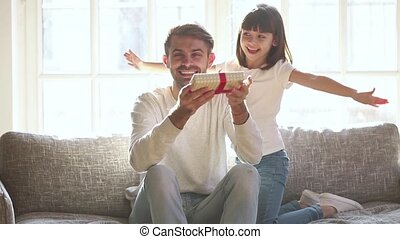 Cute child daughter congratulating daddy on fathers day...