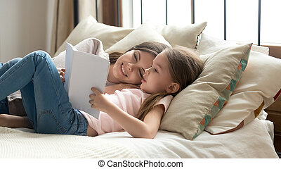 Cute child daughter holding book reading to mom in bed