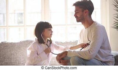 Cute child daughter holding stethoscope listening to father...
