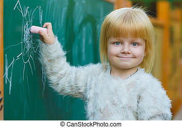 Cute child drawing with chalk on blackboard outdoor