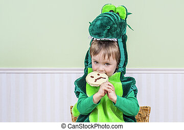 Cute child eating a Halloween cookie