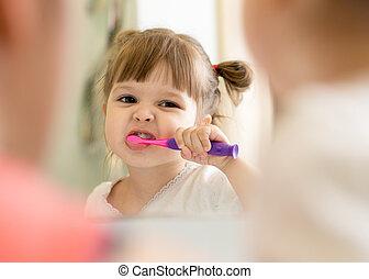 Cute child girl brushing teeth and looking in mirror in bathroom