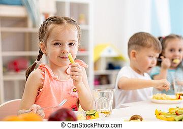 Cute child girl eats healthy food in kindergarten