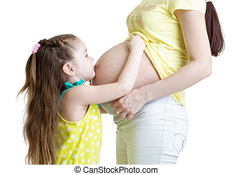 Cute child girl embracing pregnant mother belly