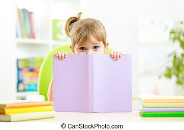 Cute child girl hiding behind book