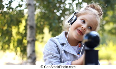 Cute child girl in headphones listening to music and singing a song in a park with birches.