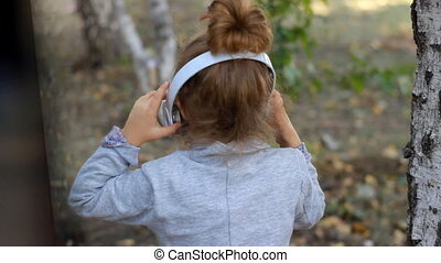 Cute child girl in headphones listening to music and singing a song in a park with birches