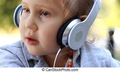 Cute child girl in headphones listening to music and singing a song. portrait closeup