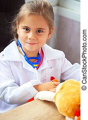 Cute child girl playing doctor with plush toy