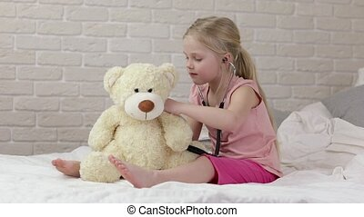 cute child girl playing doctor with teddy bear at home. girl...
