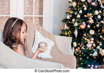 Cute child girl sitting against Christmas tree and holding sparkling Christmas ball.