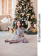 Cute child girl sitting against Christmas tree indoors.