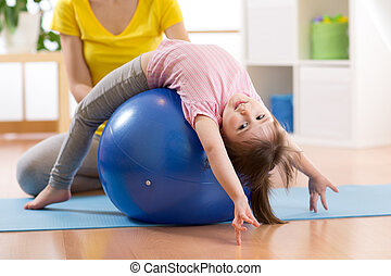 Cute child girl stretching on pilates fitness ball in gym