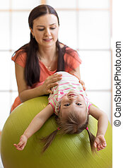 Cute child girl stretching on pilates fitness ball with mom in gym