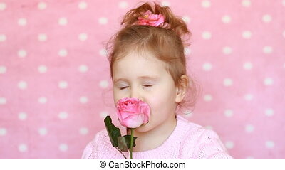 Cute child girl with a rose on a pink background. Portrait...