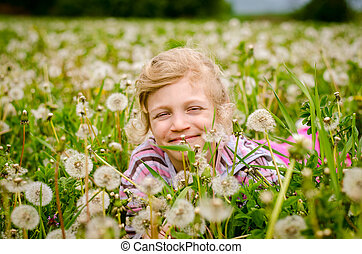 cute child in blossoming dandelion flower meadow