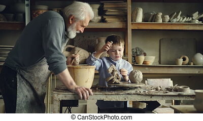 Cute child is playing with clay and potter's tools making...