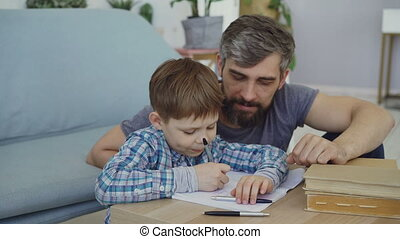 Cute child is writing in notebook with his father sitting near the table and looking at his son. Preschool education, united family, fatherhood and childhood concept.