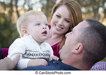Cute Child Looks Up to Sky as Young Parents Smile - Cute...