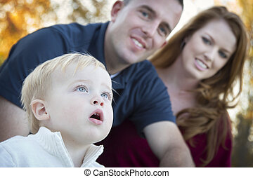 Cute Child Looks Up to Sky as Young Parents Smile