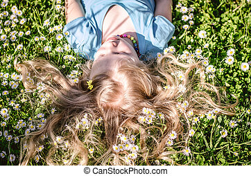 cute child lying in daisy meadow