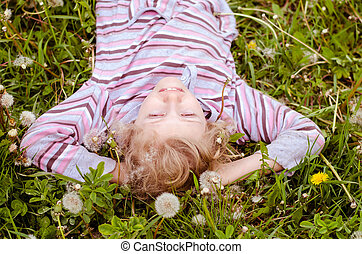 cute child lying in dandelion meadow