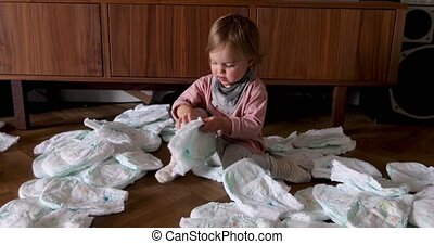 Cute child making mess with diapers - Adorable concentrated ...