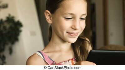 Cute child playing at tablet. Girl with tablet pc at home