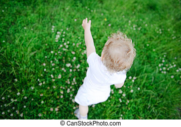 Cute child playing in green grass