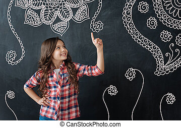 Cute child pointing to a flower and smiling