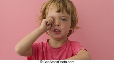 Cute child rubbing eye with plump hand - Adorable little boy...