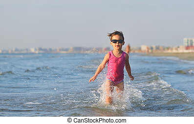 Cute child running in the waves