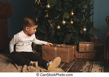 Cute child sitting near Christmas tree with gifts