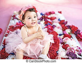 Cute child sitting on a bunch of flowers